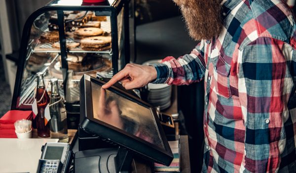 Positive bearded male at the counter using cash register in a coffee shop.